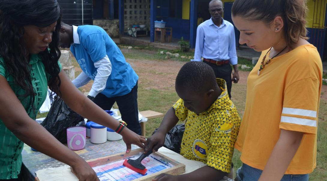 A teacher and volunteer in Ghana assist a child with an art project on a gap year program abroad.